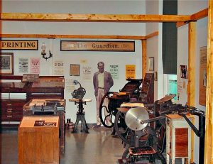 David B. Russell's printing shop and the old Bay Roberts Guardian newspaper . The printing press from the early 20th century is part of the display. Local visual artist Hilary Cass designed exhibits, including a life size depiction of David Russell.